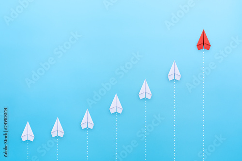 Photo  Leadership concept with red paper plane leading among white on blue background w