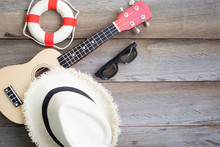 High Angle Of Life Buoy, Guitar Hat And Black Glasses With Wooden Background. Seaside Tourism Concept In The Summer