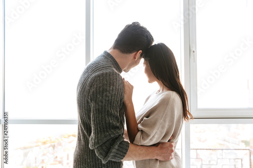 Photo  Happy young couple hugging while standing at the window