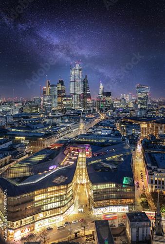 Blick über die Dächer der Skyline von London auf die City bei Nacht mit Sternenhimmel