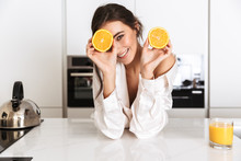 Image Of European Woman 20s Wearing Silk Leisure Clothing, Holding Two Pieces Of Orange In Kitchen