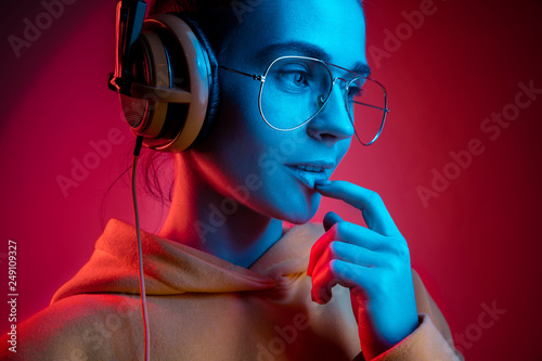 Fashion pretty woman with headphones listening to music over red neon background at studio. - 249109327