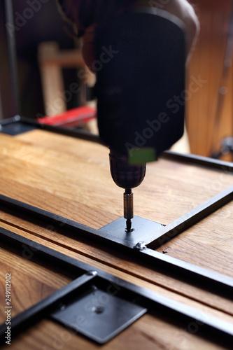 Fototapeta Produkcja mebli. Przykręcanie stelarza do drewnianego blatu. obraz