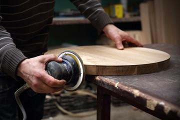Szlifowanie desek. Stolarz szlifuje drewniany blat.