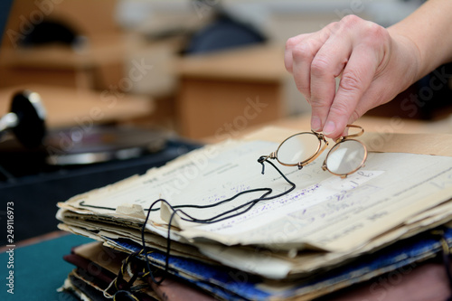 female fingers hold pince-nez over old papers Wallpaper Mural