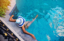 Bikini Woman In Pool Relaxing Beautiful Sexy Female Resting In Vacation On Summer Season With Hat At Resort Swimming Pool.