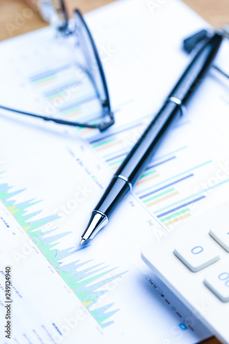 pen,glasses and calculator on Financial accounting stock market graphs analysis chart - 249124940