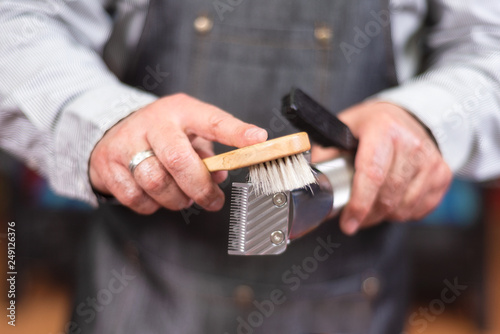 Barber cleaning electric hair clipper at barber shop. Wallpaper Mural