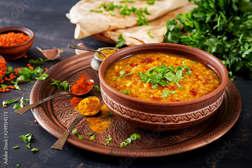Fototapeta Indian dal. Traditional Indian soup lentils.  Indian Dhal spicy curry in bowl, spices, herbs, rustic black wooden background. Authentic Indian dish. Overhead obraz