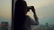 a few shots Young beautiful woman or tourist taking photograph with mobile cellphone smartphone device of skyline in Moscow Russia view from her apartment. Girl to share pic on social media photo site