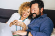 canvas print picture - Cheerful beautiful happy caucasian couple middle age at home sitting on the couch using a technology device laptop  - internet and leisure activity indoor for people smiling and enjoying the time