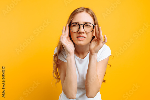 Fotografía  A girl with poor eyesight wears glasses, looking squinting, trying to figure out