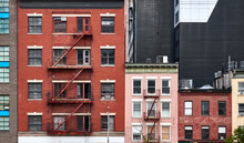 Old Tenement Houses With Fire Escapes In New York City, USA.