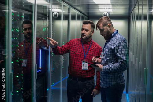 Adult bearded engineers in server room Fototapeta