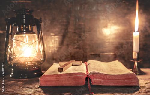 Zdjęcie XXL Biblia ze światłem świecy i lampy naftowej na drewnianym stole. chrześcijańska koncepcja.