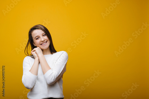 Fotografie, Obraz  Kind young girl looking smiling into camera leaning her head on her hands against yellow background