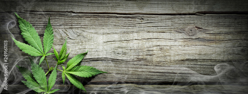 Photo  Cannabis Sativa Leaves With Smoke On Wooden Table - Medical Legal Marijuana