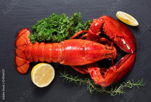 Czerwony homar z cytryną i zielenią na czarnym drewnianym tle