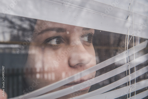 Fotografia Woman Looking Through the Blinds. Girl looking out the window