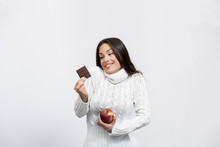 Beautiful Young Woman In A Studio With An Apple And Chocolate