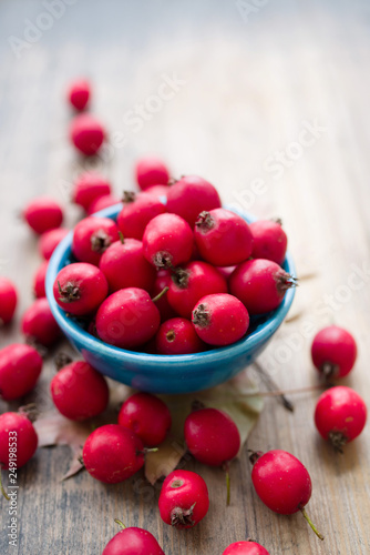 Fotografia Hawthorn tincture in a blue small bowl and fresh hawthorn fruit on the wooden surface of the table