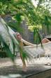 Pensive woman relaxing in hammock in the garden