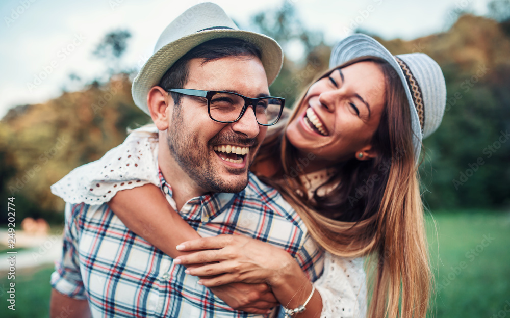 Fototapeta Meeting in the park. Boyfriend carrying his girlfriend on piggyback. Love, dating, romance