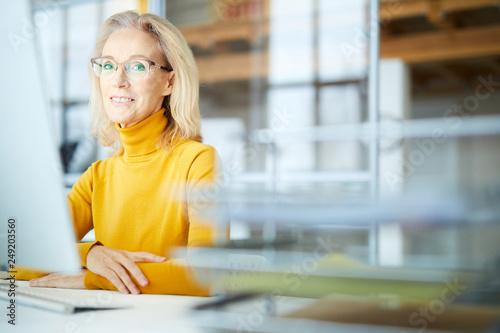 Valokuva  Portrait of elegant mature businesswoman looking at camera and smiling while usi