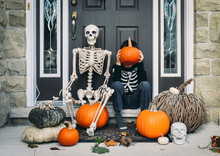Boy Covering Face With Pumpkin While Sitting By Skeleton During Halloween