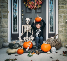 Portrait Of Smiling Boy Holding Pumpkin While Sitting With Skeleton Near Door