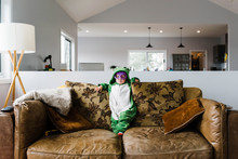 Cute Girl In Frog Costume Standing On Sofa At Home During Halloween