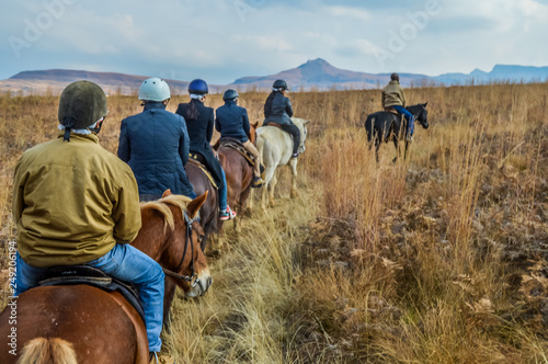 Fototapeta Group of Indian Horse riding riders on a trail in Drakensberg re