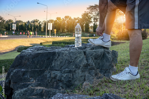 Fotografía  Close up of legs senior man tying shoe laces on stone with water bottle