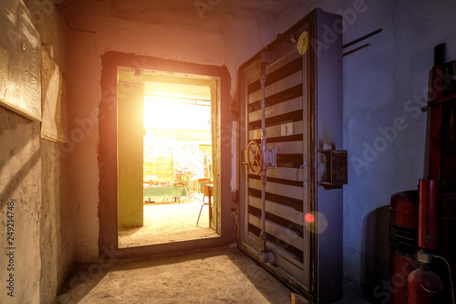 Photo  Opened hermetic metal armored door with valve, entrance of bomb shelter protecti