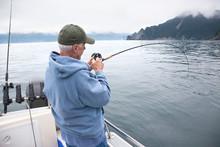 Senior Fisherman Reeling In A Fish Near Seward, Alaska