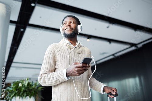 Happy young casual traveler with smartphone and headphones listening to his favo Canvas Print
