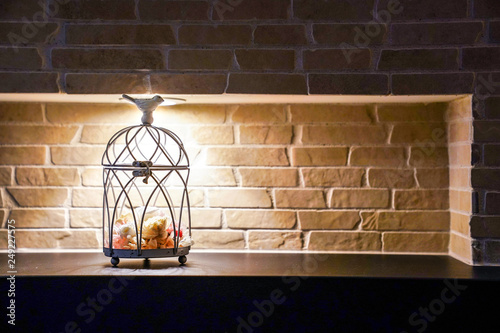 Fotografie, Obraz  flower inside bird cage and bird object over it; home decoration with tungsten light and brick wall