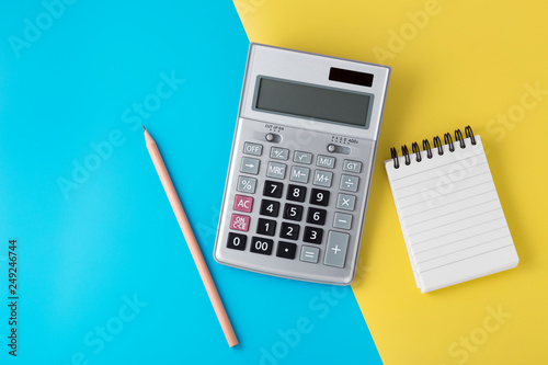 Fotografía  Calculator and notepad on light blue and yellow background