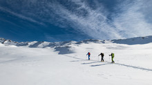 Three Friends During A Ski Mountaineering Trip On The Trail