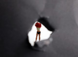 Miniature woman. The back of a woman who is changing her clothes that are seen through a small hole.