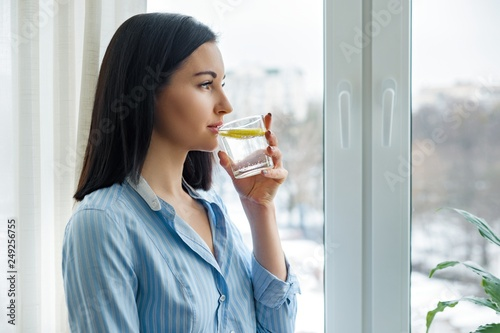 Fototapeta Young woman morning at home near the window drinking water with lemon, vitamin drink in winter spring season obraz