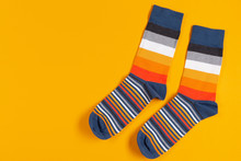 Two Multi-colored Striped Socks Lie On A Yellow Background