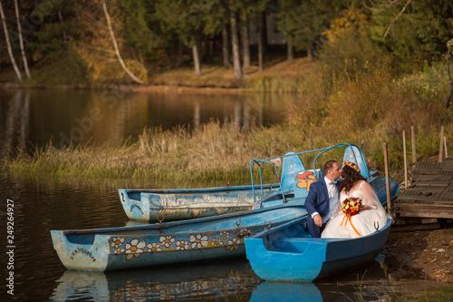 Foto  Beautiful wedding couple posing in boat on lake