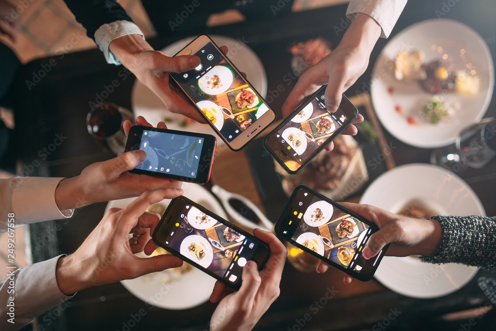Fototapety, obrazy: Group of friends going out and taking a photo of food together with mobile phone