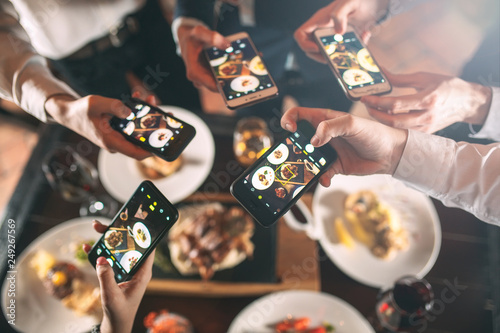 Photo  Group of friends going out and taking a photo of food together with mobile phone