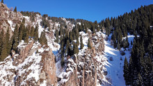 Large Rock Covered With Snow. Around Are Pine Trees, Firs And Spruce. Clear Blue Sky. Snow Gorge. Shooting From A Drone From The Air. Mountainous Area