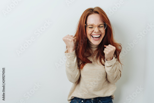 Canvas Print Exuberant young woman cheering and punching air