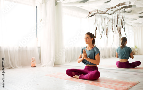 mindfulness, spirituality and healthy lifestyle concept - woman meditating in lotus pose at yoga studio