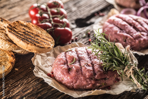 Fotografía  Raw burgers on wooden table with onion tomatoes herbs and spices