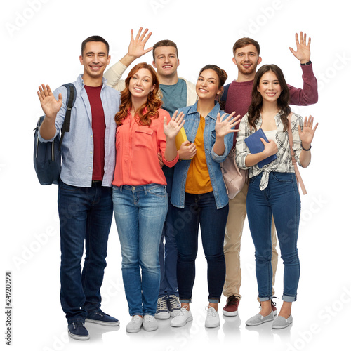 education, high school and people concept - group of smiling students with books waving hands over white background